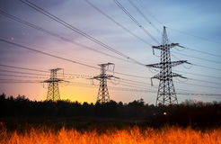 High voltage power tower and silhouette power lines sunset. Royalty Free Stock Images