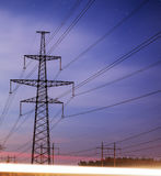 High voltage power tower and silhouette power lines sunset. Royalty Free Stock Photos