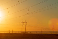 High-voltage power transmission line. Energy pillars. At sunset, Stock Image