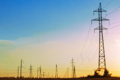 High-voltage power transmission line. Energy pillars. At sunset, Royalty Free Stock Photos