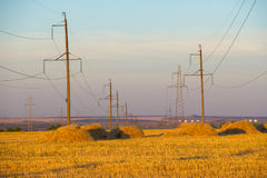 High-voltage power transmission line. Energy pillars. At sunset, Royalty Free Stock Images