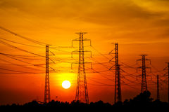 High voltage power transmission lines and pylons. Silhouette of high voltage power transmission lines and pylons at sunset, Thailand Royalty Free Stock Photos
