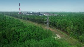 High-voltage power transmission lines tower on a dirty coal-fired, carbon dioxide-emitting factory. Drone aerial view