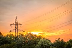 High voltage power transmission tower with electrical energy wir. Es at sunset Royalty Free Stock Photos