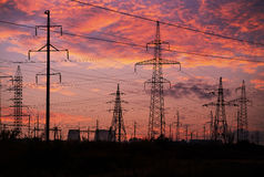 High-voltage power transmission towers. In sunset sky background Stock Images