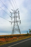 High voltage powerline tower with road in forground. Royalty Free Stock Image