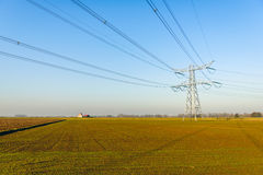 High voltage pylon and cables in a flat landscape Stock Photos