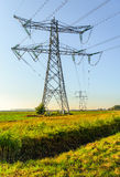 High voltage pylons and cables in a rural area Stock Images