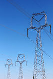High voltage pylons under blue sky Stock Photo