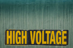 High Voltage Sign. Black and yellow High Voltage sign on side of green electrical box Royalty Free Stock Photo