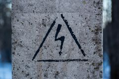 High voltage sign on a concrete pillar. Black sign on a white wall Royalty Free Stock Images