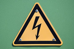 High voltage sign. On a green metal surface Royalty Free Stock Photo