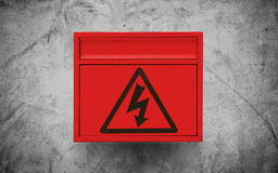 High voltage sign symbol, on red electronic box on concrete wall texture background Royalty Free Stock Image