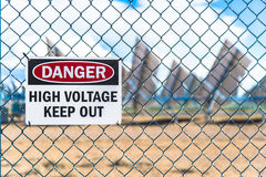 High Voltage Solar Panel Danger Sign. Alternative energy solar panel cells in the background with a danger high voltage keep out sign on a chain link fence Royalty Free Stock Photography