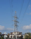 High-voltage support against the sky. High voltage towers against the sky and individual houses Stock Photo