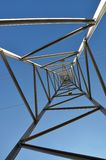 High voltage tower 1-looking up. View up within a high voltage tower against blue sky stock images