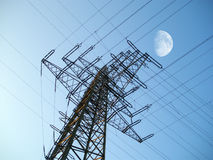 High voltage tower. Electric high voltage tower and moon on sky Royalty Free Stock Photos