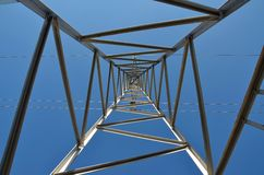 High voltage tower 2-looking up. View up within a high voltage tower against blue sky stock photos