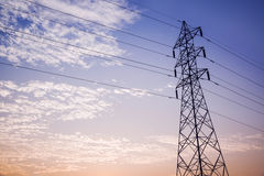 High voltage tower in cloud and blue sky. Royalty Free Stock Photo