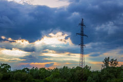 High-voltage tower dark dramatic clouds sun`s rays. High-voltage tower against the dark dramatic clouds through which the sun`s rays make their way Royalty Free Stock Image