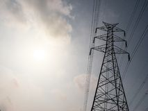 High voltage tower or electricity transmission power lines in the cloudy blue sky Stock Photos