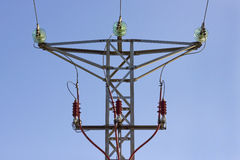 High voltage tower. Front view of the top of a high voltage tower with a cloudless blue sky Stock Image
