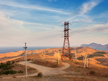 High voltage tower in mountains at sunset. Electricity pylon sys Royalty Free Stock Photo