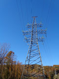 High voltage tower and power line. In forest area Stock Images