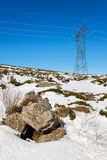 High voltage tower. On a snowy landscape Royalty Free Stock Photo