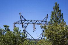 High voltage tower. Top of high voltage tower peeking through the tree tops Stock Photography