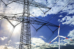 High voltage tower and wind turbine  line in the sky Royalty Free Stock Photos