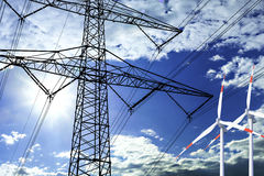 High voltage tower and wind turbine  line in the sky Royalty Free Stock Images
