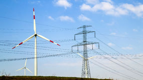 High voltage tower and wind turbines against blue sky Stock Photos