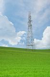 High-voltage towers and cables in agricultural fields on a blue sky Royalty Free Stock Images