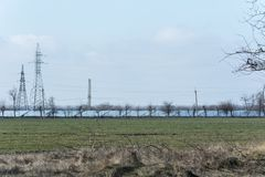 High-voltage towers power lines and lines of solar panels. In the field Stock Photos