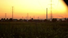 High-voltage towers at sunset near the houses. High-voltage tower in the sunset near the houses the view from the window of the car in motion stock video footage