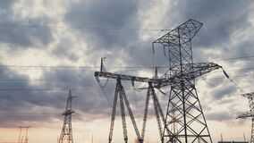 High voltage towers at sunset in the sky, high voltage power grids, electrical volt installations, uniform distribution