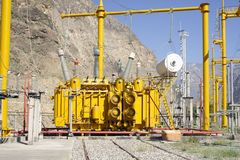 High voltage transformer. At power plant. Mountain and blue sky Stock Images