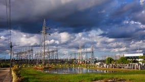 High voltage transformer substation against blue sky Stock Photos