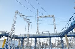 High-voltage transformers and power line supports. blue sky without clouds. Power station. Royalty Free Stock Images