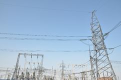 High-voltage transformers and power line supports. blue sky without clouds. Power station. Stock Photos