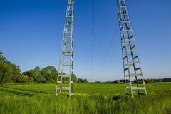 High voltage transmission line. Beautiful view of landscape with green fields, green forest trees and blue sky. Gorgeous backgrounds. Sweden. Europe stock photography