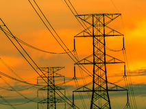 High voltage transmission line on the metal tower. On sunset sky background stock photos