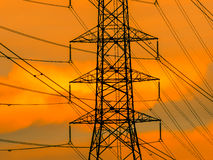 High voltage transmission line on the metal tower. On sunset sky background stock image