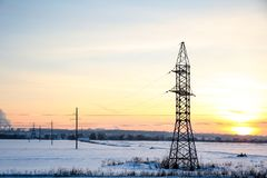 High-voltage transmission line in winter at sunset. High voltage line support is on the field in winter. power line support on a cold winter evening stock photos