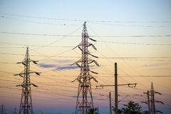 High voltage transmission lines. For elecrticity during sunset Royalty Free Stock Images