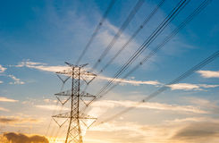 High voltage transmission lines on orange and blue sky, sunrise Royalty Free Stock Photography