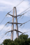 High-voltage transmission tower. Against blue cloudy sky background royalty free stock photo