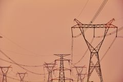 High voltage transmission tower. In the dusk pink sky, the high-voltage transmission towers are standing like giants royalty free stock photography
