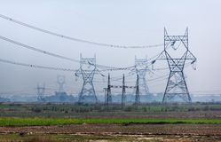 High voltage transmission towers line as gigantic owls. Transmission towers of lines of high voltage similar to very big owls and other exotic mythical animals Royalty Free Stock Photography